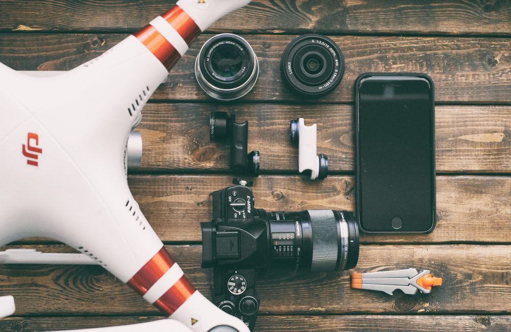 Drone laying on a table with camera and other photography equipment